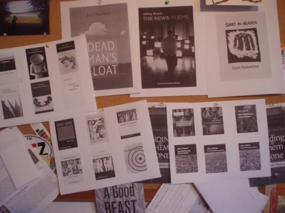 Bulletin board wit lots of cover designs printed and posted all over it.